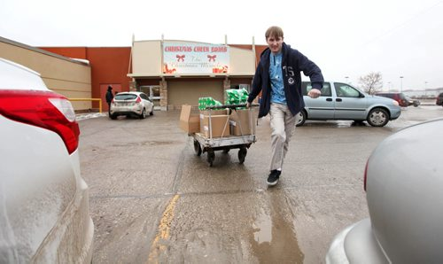 Brett Ryall brings a cart full of hampers to his 2 door Sunfire that he will pack full before heading out to delivery them.     Feature story on the Christmas Cheer Board.  Dec 20, 2014 Ruth Bonneville / Winnipeg Free Press