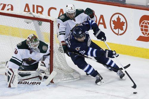 Winnipeg Jets' Blake Wheeler (26) attempts the wrap-around against Minnesota Wild goaltender Devan Dubnyk (40) as Wild's Marco Scandella (6) defends during first period NHL action in Winnipeg on Tuesday, February 10, 2015. (John Woods / WINNIPEG FREE PRESS)