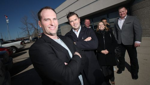 TIM COMACK, (2nd from left) vice-president of development for Ventura Land Company and Ventura Developments Inc., and PETER GROSE, (left) president of Westland Construction. Their companies have purchased this 19,537-square-foot building from FWS, and will begin moving in this summer after FWS relocates to larger quarters in the Tuxedo Business Park. Left to right behind them are Cliff Penner Glenda Sobie, Jonathon Freed and Arin Comack. Murray McNeill story. March 13, 2015 - (Phil Hossack / Winnipeg Free Press)