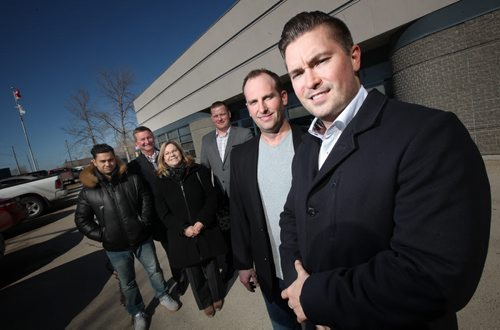 TIM COMACK, (Right) vice-president of development for Ventura Land Company and Ventura Developments Inc., and PETER GROSE, (2nd from right) president of Westland Construction. Their companies have purchased this 19,537-square-foot building from FWS, and will begin moving in this summer after FWS relocates to larger quarters in the Tuxedo Business Park. Left to right behind them are Jonathon Freed, Cliff Penner Glenda Sobie, and Arin Comack. Murray McNeill story. March 13, 2015 - (Phil Hossack / Winnipeg Free Press)