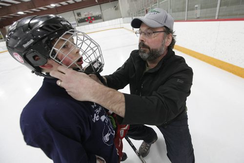 March 30, 2015 - 150330  -  Troy Titterson puts a helmet on his son Finley at a spring hockey camp Gateway Arena Monday, March 30, 2015. A recent study shows that hockey helmets are not good at protecting against concussions. John Woods / Winnipeg Free Press