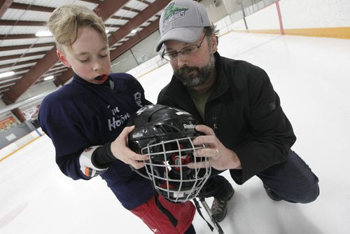 March 30, 2015 - 150330  -  Troy Titterson with his son Finley check out his helmet at a spring hockey camp Gateway Arena Monday, March 30, 2015. A recent study shows that hockey helmets are not good at protecting against concussions. John Woods / Winnipeg Free Press