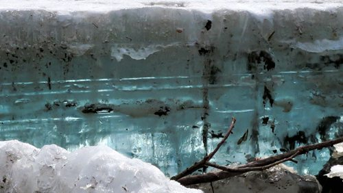 A large chunk of  crystal blue ice seems out of context  amidst the grey and black muddy waters and ice surrounding in the  Assiniboine River near the Legislative Building Tuesday afternoon.   April 7, 2015 Ruth Bonneville / Winnipeg Free Press.