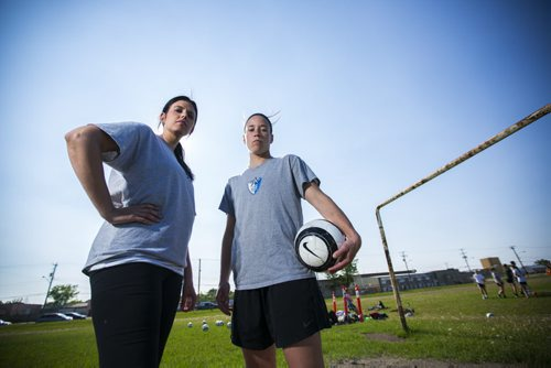 Soccer's Best manager Dana Kuhl (left) and Goalkeeper Chandra Bednar stand on a soccer field in the West End of Winnipeg on Wednesday, June 10, 2015.  Bednar has been playing for 15 years, and is hoping to go pro in Europe soon, but practicing on the hard dirt scrapes her elbows every time she dives to save the ball. Mikaela MacKenzie / Winnipeg Free Press