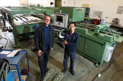 Micro Tool & Machine Ltd. makes sophisticated transformer manufacturing machines. They have exported to about 40 countries. It's getting ready to ship a big innovative new machine to China which could have an impact on the industry. (L-R) Gord Atamanchuk and Andrew Chan pose for a photo with the that machine. BORIS MINKEVICH/WINNIPEG FREE PRESS June 15, 2015