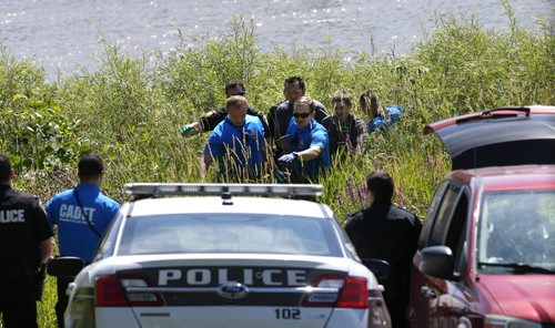 A body of a male is carried to a van,  the body was found Wednesday morning in Red River close to the Alexander Dock. This is connected to a incident on July 14, shortly after 9:30 p.m. when the Winnipeg Police Service received several reports of a male in the river near the Provencher Bridge, the  River Patrol and members of the Winnipeg Fire Paramedic Services attended however were unable to locate the male.  Aidan Geary story story Wayne Glowacki / Winnipeg Free Press July 22 2015
