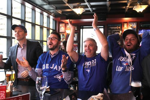 Toronto Blue Jays baseball fans react with first joy, then disappointment when the Jays missed an opportunity to tie up the game against Texas in the 6th inning on TV  at the Pint Thursday afternoon.   Names from left - Ross McFadyen (hat, suit jacket), Scott Hoeppner (glasses, jersey), Glen Agar (white hair, centre) and Chris Stanton (hat, jersey, cape).   Oct 08, 2015 Ruth Bonneville / Winnipeg Free Press