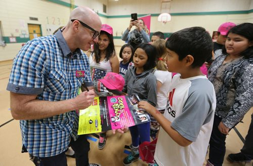 Virgin 103.1 FM radio host Ace Burpee signs a poster for Grade 5 student Jayden Hunter-Park at Ralph Brown School during the launch of the fourth annual Winnipeg Police Association Cool 2Be Kind anti-bullying campaign. Photo by Jason Halstead/Winnipeg Free Press RE: Standup photo