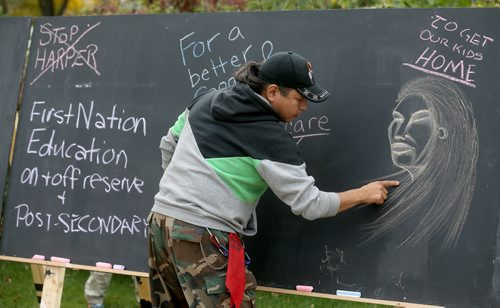 Chad Reeves does a chalk drawing at the Legislative Building at the Goodbye Harper Happy Dance, Saturday, October 10, 2015. (TREVOR HAGAN/WINNIPEG FREE PRESS)