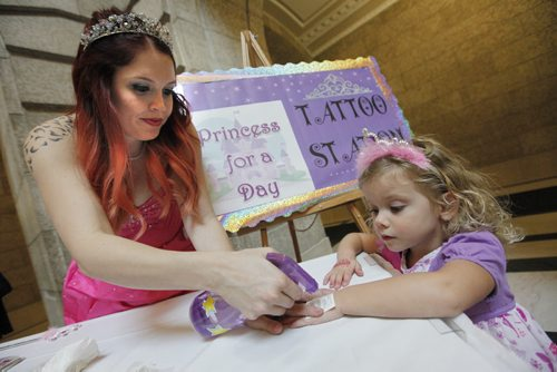"""October 18, 2015 - 151018  -  Princess Pamela Fernandez tattoos  Princess Khloe Line, (3) with a princess tattoo at the Princess For A Day fundraising event  for the Children's Wish Foundation at the Manitoba Legislature Sunday, October 18, 2015.  Princess for a Day Provides Fun, Fantasy for Little Girls with Life-Threatening Diseases. Approximately 100 little girls, including 40 battling life-threatening or chronic illnesses, will each soon be crowned """"Princess for a Day"""" as part of a unique fundraising event for the Children's Wish Foundation – Manitoba and Nunavut.   John Woods / Winnipeg Free Press"""
