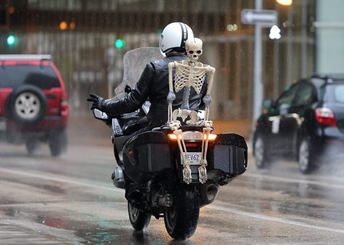 "Paul Peters rides his motorcycle on York Avenue downtown with a replica skeleton (Peters calls him ""Gord"") on Oct. 31, 2015. Photo by Jason Halstead/Winnipeg Free Press"