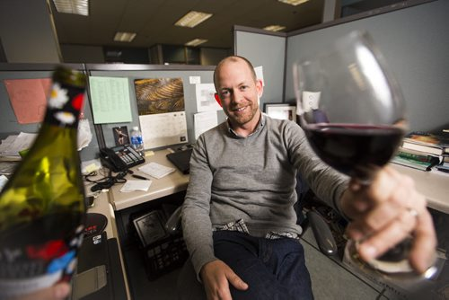 Ben MacPhee-Sigurdson, who has been the Free Press wine columnist for 10 years, tries this year's Beaujolais Nouveau vintage in the newsroom in Winnipeg on Thursday, Nov. 19, 2015.   (Mikaela MacKenzie/Winnipeg Free Press)