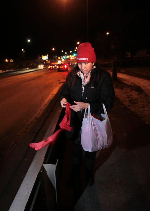 "Althea Guiboche places ribbons along the guard rails of the Slaw Rebchuk bridge Monday evening. The Red RIbbon Project she's spearheading is to honor of all of the Missing and Murdered of Canada, Althea Guiboche ""The Bannock Lady"" will be leading a red cloth memorial project for the bridges around Winnipeg. See Ashley Prest story. December 14, 2015 - (Phil Hossack / Winnipeg Free Press)"