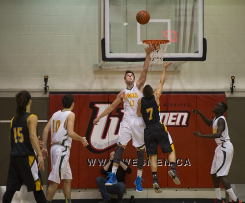 DAVID LIPNOWSKI / WINNIPEG FREE PRESS 151230  John Taylor Pipers James Wagner (#11) blocks shot by Garden City's Fighting Gophers Cole Penner (#7) December 30, 2015 as the Pipers defeated the Fighting Gophers during the 49th Wesmen Classic High School Final at the Duckworth Centre.