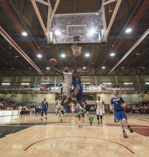 DAVID LIPNOWSKI / WINNIPEG FREE PRESS 151230  University of Manitoba Bisons Ilarion Bonhomme II (#5) goes up against Lakehead University Thunderwolves Bacarius Dinkins (#24) Wednesday December 30, 2015 during the 49th Wesmen Classic University Final at the Duckworth Centre.