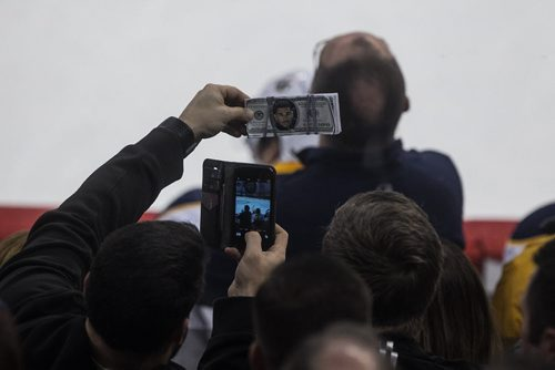 A fan holds up some fake money with former Jet Evander Kane on it while Kane stands at his bench between plays. Winnipeg Jets vs Buffalo Sabres during first period NHL action in Winnipeg on Sunday, January 10, 2016. 160110 - Sunday, January 10, 2016 -  MIKE DEAL / WINNIPEG FREE PRESS