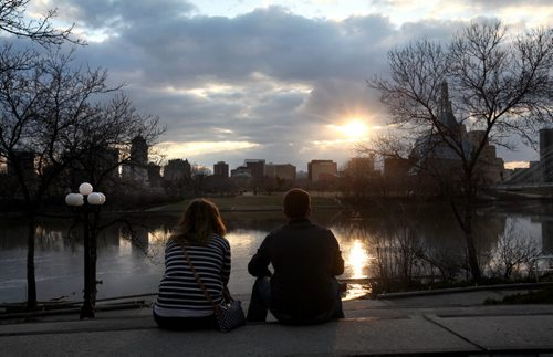 RUTH BONNEVILLE / WINNIPEG FREE PRESS  Andrea-Anne Boisvert and her friend Aarron Bickerstaff enjoy the spectacular view of the sun shining through the clouds reflected on the Red River from Tache Promenade Wednesday evening.  Standup photo  APRIL 20, 2016