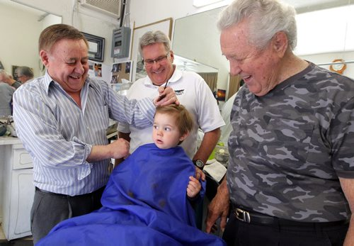 BORIS MINKEVICH / WINNIPEG FREE PRESS (left) Barber Rocky Curatola of Rocky's Men's Hair Styling cuts a fifth generation customer Lincoln Alto, just shy of 2 years old, while grandpa (centre) Dr. Lauri Alto, 61, and great grandpa (right) Olie Alto, 87, watch on. This is the boys 3rd haircut. The boys dad couldn't make it down for the photo because of work, but grandpa and great gramps were happy to help pass down the family tradition. Photo taken at the barber shop's current location at 290 Pembina Highway. May 19, 2016.