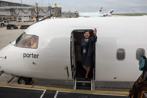 MIKE DEAL / WINNIPEG FREE PRESS Flight attendant Patricia Marzec waves as the Porter Airline flight for Toronto leaves Winnipeg. Marzec has been with Porter since it started in 2006. 160529 - Sunday, May 29, 2016