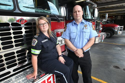 JOE BRYKSA / WINNIPEG FREE PRESS  Scott Wilkinson- Wpg Fire Dept . Academy Training officer, and CISM fire coordinator,right, and Jennifer Lundin- Advanced Care Paramedic, and CISM coordinator for EMS- pose for photo next to fire trucks in Winnipeg's downtown fire/ambulance station - July 14, 2016 -(See Mike McIntyre story)