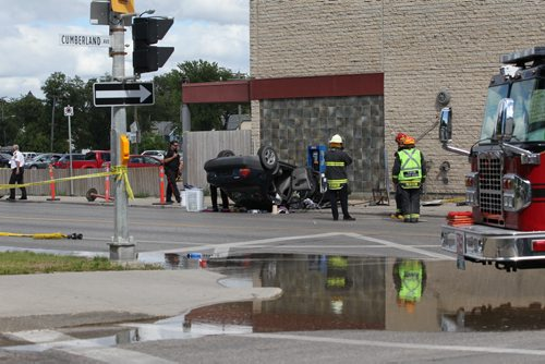 RUTH BONNEVILLE  / WINNIPEG FREE PRESS  A vehicle is seen flipped upside down after appearing to have hit a fire hydrant, light standard and hydro lines to the Balmoral Hotel   closing traffic during rush hour along Balmoral at Cumberland Friday afternoon.    Aug 12 / 2016