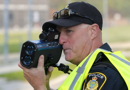 BORIS MINKEVICH / WINNIPEG FREE PRESS SCHOOL ZONE SPEED ENFORCEMENT - Const. Ray Howes enforces the 30km/hr school zone on Bannatyne Ave. near Lydia Street. The fastest car in the zone was 61km/hr  when the photog was there, and it was a teacher that was driving. Here he uses the speed laser gun.  Sept. 1, 2016