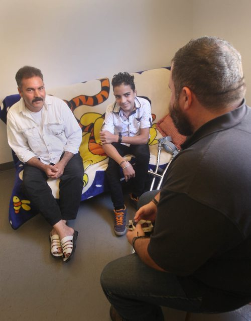 JOE BRYKSA / WINNIPEG FREE PRESSSyrian refugees/ New Canadians -Sleman Sarahan, and his son Ibrahim , 14 years chat with Joel Muller, right, a match program volunteer at Welcome Place.  Sept 22, 2016 -(See Carol Sanders story)