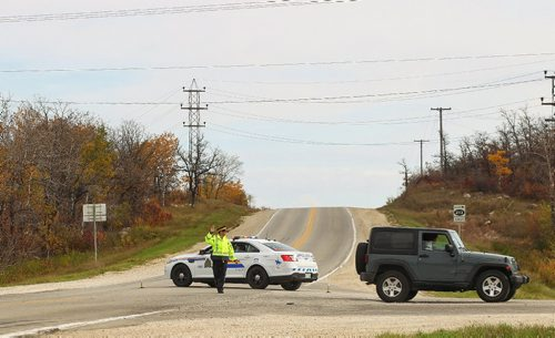 MIKE DEAL / WINNIPEG FREE PRESS  An RCMP officer directs traffic on Hwy 213 (Garven Road) at the intersection with Hwy 207. The driver of a pickup truck was in a head on collision with a gravel truck Monday morning.   161003 Monday, October 03, 2016