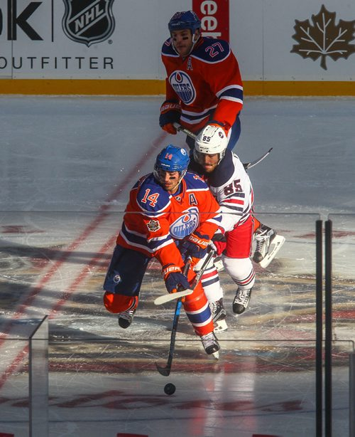 MIKE DEAL / WINNIPEG FREE PRESS Winnipeg Jets' Mathieu Perreault (85) and Edmonton Oilers' Jordan Eberle (14) battle for the puck in the unusual light hitting the ice during the NHL game between the Winnipeg Jets and the Edmonton Oilers at Investors Group Field. 161023 - Sunday October 23, 2016