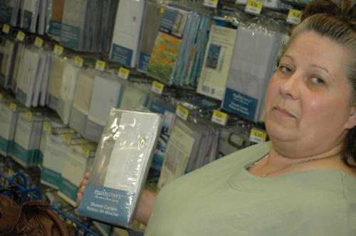 """Shelley Seidl, a shopper at a Winnipeg Walmart, shown holding a PVC shower curtain. A report released today by the U.S.-based Centre for Health, Environment and Justice said PVC curtains such as those shown here may be releasing toxic compounds into people's homes. """"I'll have to try something else,"""" Seidl said. June 12, 2008. By Will Tremain Winnipeg Free Press"""