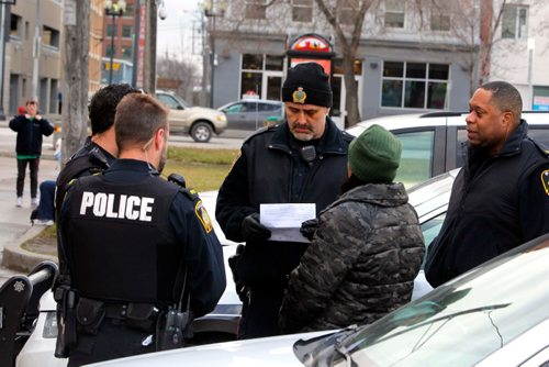 BORIS MINKEVICH / WINNIPEG FREE PRESS MAIN STREET BEAT COP - Main street beat cop Kevin Burkett walks the beat on Main Street near Henry. Police often make arrests and if Burkett, centre wearing a toque,  is handy he helps out. Nov. 16, 2016
