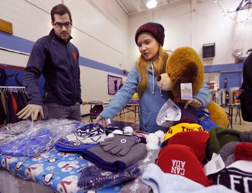 WAYNE GLOWACKI / WINNIPEG FREE PRESS  Raelynn Beaton, a grade 9 student, looks for gifts for her family  with help from James Campbell with Think Shift at the pop-up  set up in the R. B. Russell Vocational High School Thursday. The store is put on by Think Shift, a local marketing company, which donates everything for the event to give less fortunate kids a chance to shop, for free, for Christmas gifts for their families. Ashley Prest story.  Dec.15 2016