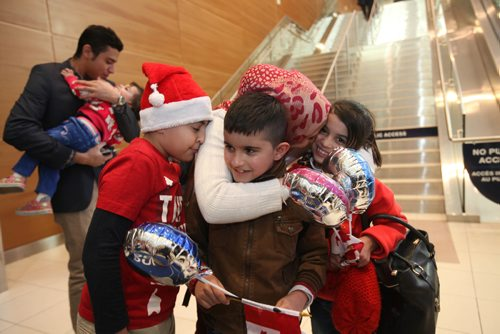 RUTH BONNEVILLE / WINNIPEG FREE PRESS   Winnipegger Zainab Ali hugs her twin niece and nephew eight-year-old  Mohammad and Zainab Al Ali  after they arrive with their parents, Khaled, his wife Muntaha and their little sister Naya (20mnths) at James Richardson International Airport Thursday afternoon. Her son eight-year-old Mahammad Chaeban (santa hat) welcomes them with her while Tiba Al Abdellah, the children's uncle hugs his niece Naya Al Ali (20mnths) in the background.   See Carol Sanders story.    Dec 29, 2016