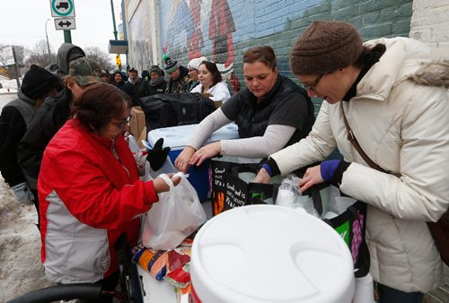 "JOHN WOODS / WINNIPEG FREE PRESS On Dufferin at Main, Kim Gulak (c), Nicole Stonyk (r), and other ""Bannock Army"" volunteers assist Althea Guiboche, AKA ""The Bannock Lady"", feed local people Sunday, January 22, 2017. Guiboche and her crew of dedicated supporters are marking four years of feeding local people."