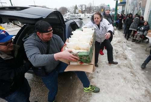 """JOHN WOODS / WINNIPEG FREE PRESS On Dufferin at Main, Sonia Korchynski (c), and other """"Bannock Army"""" volunteers assist Althea Guiboche, AKA """"The Bannock Lady"""", feed local people Sunday, January 22, 2017. Guiboche and her crew of dedicated supporters are marking four years of feeding local people."""