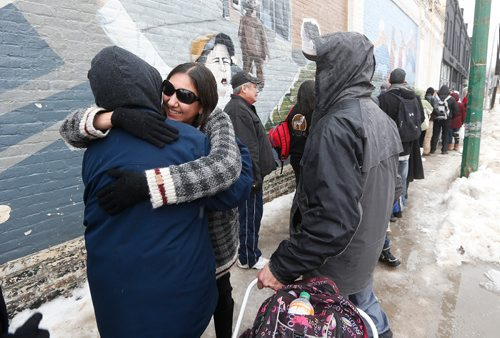 "JOHN WOODS / WINNIPEG FREE PRESS On Dufferin at Main, Althea Guiboche, AKA ""The Bannock Lady"", hugs people who line up to receive food Sunday, January 22, 2017. Guiboche and her crew of dedicated supporters are marking four years of feeding local people."