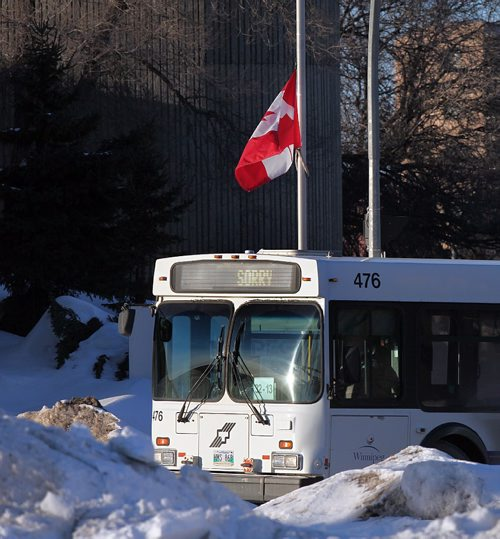 PHIL HOSSACK / WINNIPEG FREE PRESS  -   A city transit bus pulls into the city garage and headquarters on Osborne street south past a flag at half mast mourning the loss of a driver after a deadly assault.   See story.  - February 13, 2017
