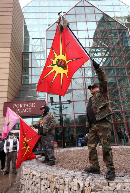 RUTH BONNEVILLE  / WINNIPEG FREE PRESS  Denny Wood (left) and Vern DeLaronde (front, right) part of an activist group called the Urban Warrior Alliance, hold flags in area in back of Portage Place Shopping Centre Saturday, a known drug-dealing site, to stand up against dealers in the area that are making it unsafe for people,  See Bill Redekop story.   March 25, 2017
