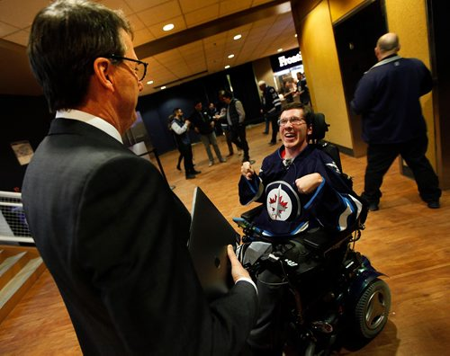 """PHIL HOSSACK /WINNIPEG FREE PRESS - """"Luke"""" (sorry only have his first name) meets Mark Chipman before the Jets and Ducks game Thursday.Chipman presented him with game tickets and a signed Dustin Byfuglien jersey. See Jenn Z's story.  March 30, 2017   (Robb Nash has helped save the lives of 100s of kids — including Luke. Luke is in a wheelchair. He was going to take his life and the Robb Nash Project was able to help him. He is doing so much better now and helping inspire other kids now with his own motivational videos. Tonight, Robb is surprising Luke with tickets to tonight's Jets game as well as some signed merch courtesy of Mark Chipman. I'll be writing a column on Friday, but tonight is a great op to get a photo of Luke.  Jen Zoratti story)"""