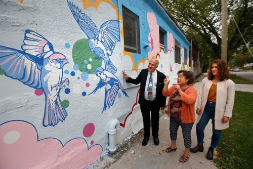 WAYNE GLOWACKI / WINNIPEG FREE PRESS   Tom Ethans, Take Pride Winnipeg! and Orycia Karpa with the Ukrainian Canadian Congress listen to Sung Hee Kim, centre, who helps run her family convenience store Five Star Foods on the corner of Powers Street and Burrows Ave. speak about the life energy and hope she feels from the mural painted on her store. Take Pride Winnipeg! partnered with the Ukrainian Canadian Congress to make this project materialize. The mural officially unveiled Thursday was designed and painted by muralist Gabrielle Funk, with assistance from children in the neighbourhood.  Sept. 21 2017