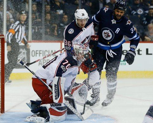 JOHN WOODS / WINNIPEG FREE PRESS Winnipeg Jets' Dustin Byfuglien (33) and Columbus Blue Jackets' Zac Dalpe (36) look on as the Jets' shot gets past goaltender Joonas Korpisalo (70) during second period NHL action in Winnipeg on Tuesday, October 17, 2017.