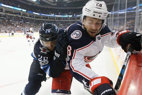 JOHN WOODS / WINNIPEG FREE PRESS Winnipeg Jets' Blake Wheeler (26) checks Columbus Blue Jackets' Oliver Bjorkstrand (28) during second period NHL action in Winnipeg on Tuesday, October 17, 2017.