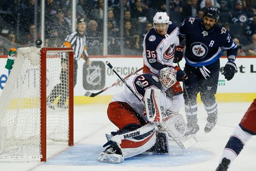 JOHN WOODS / WINNIPEG FREE PRESS Winnipeg Jets' Dustin Byfuglien (33) and Columbus Blue Jackets' Zac Dalpe (36) look on as the Jets' shot gets past goaltender Joonas Korpisalo (70) during second period NHL action in Winnipeg on Tuesday, October 17, 2017.