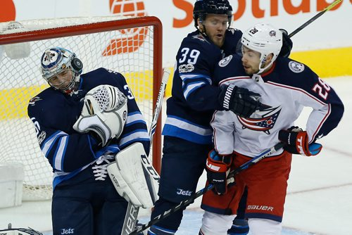 JOHN WOODS / WINNIPEG FREE PRESS The Columbus Blue Jackets' shot goes off the mask of goaltender Steve Mason (35) as Toby Enstrom (39) defends against Columbus Blue Jackets' Oliver Bjorkstrand (28) during first period NHL action in Winnipeg on Tuesday, October 17, 2017.