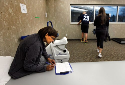 PHIL HOSSACK / WINNIPEG FREE PRESS  - Knee replacement patient Shanti Temull fills out a record of her workout Monday as Physio Therapist Jasmine Thorsteinson walks towards the next station at the Reh-Fit. See Jane Gerster's story re: Group Physiotherapy.   - November 20, 2017
