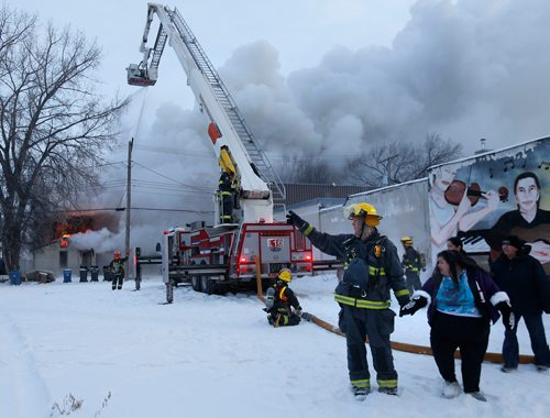 WAYNE GLOWACKI / WINNIPEG FREE PRESS   A Winnipeg Fire Fighter assists a  Pritchard Ave. resident who lives nearby the three storey rooming house fire Friday morning. The fire in the 200 block of Pritchard Ave. started approximately 7A.M.   Dec. 29  2017