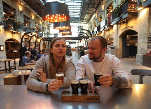 RUTH BONNEVILLE / WINNIPEG FREE PRESS  Biz story on Forks developments. Sasha Podgorng (right) shares some craft beer with his friend Eva Dugova visiting from Slovakia at the Forks Common Friday afternoon.   Jan 12, 2018