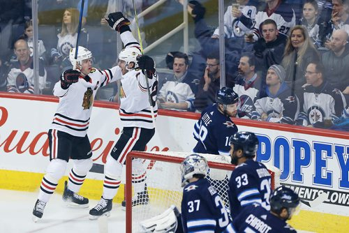 Chicago Blackhawks' Jonathan Toews (19) and Brandon Saad (20) celebrate Saad's goal against Winnipeg Jets goaltender Connor Hellebuyck (37) 11 seconds into the first period NHL action in Winnipeg on Thursday, March 15, 2018. THE CANADIAN PRESS/John Woods