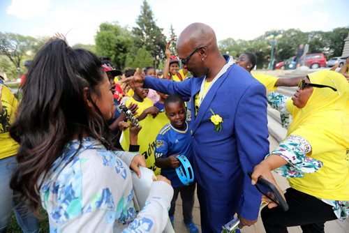 TREVOR HAGAN / WINNIPEG FREE PRESS Ken Opaleke, executive director of the West Broadway Youth Outreach organization is mobbed after he, and 11 others received the Order of Manitoba during a ceremony at the Legislative Building, Thursday, July 12, 2018.