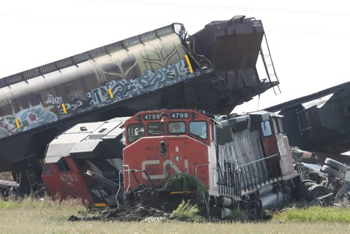 Brandon Sun 04092009 Grain cars and locomotives from a CN train lie in a twisted wreck after the train struck a semi trailer at a railway crossing on Rd. 58 N south of Carberry, Man. on Friday morning. No one was injured in the accident which crushed the second rig of the double-long semi and derailed the train. (Tim Smith/Brandon Sun)